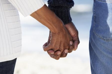 genegenheid: Close-up Van Senior bedrijf paar handen op het strand Stockfoto