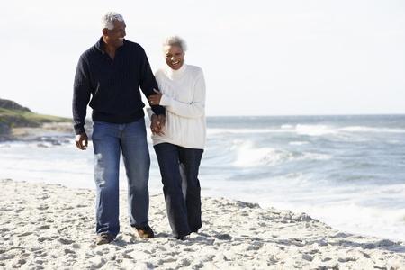 black lady talking: Senior Couple Walking Along Beach Together
