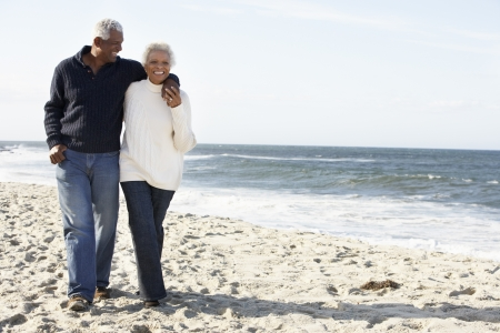 beach front: Senior Couple Walking Along Beach Together