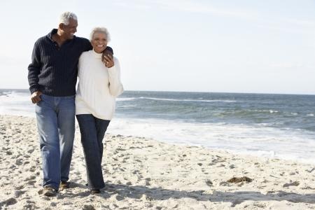 black couple: Senior Couple Walking Along Beach Together