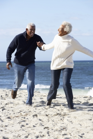 american seniors: Romantic Senior Couple Running Along Beach