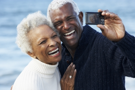 Senior Couple With Camera On Beach Stock Photo - 18736039