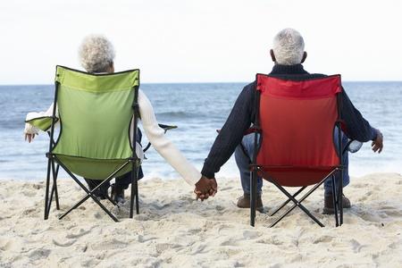parejas enamoradas: Senior pareja sentada en la playa Deckchairs En