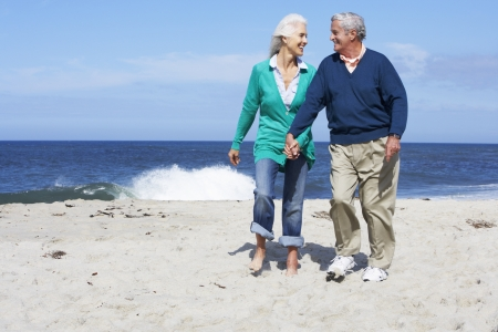 Senior Couple Walking Along Beach Together photo