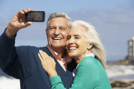 Senior Couple With Camera On Beach photo