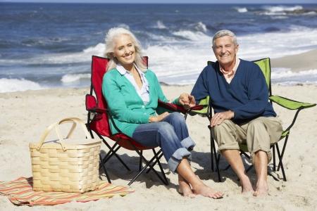 Senior paar zittend op het strand in ligstoelen die Picknick Stockfoto