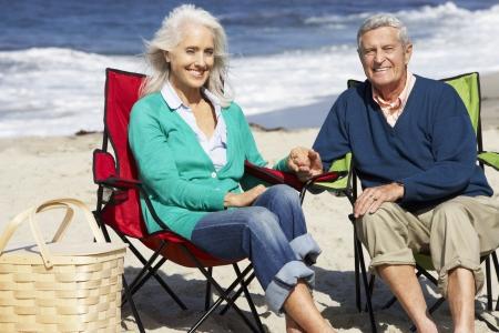 Senior Couple Sitting On Beach In Deckchairs Having Picnic photo