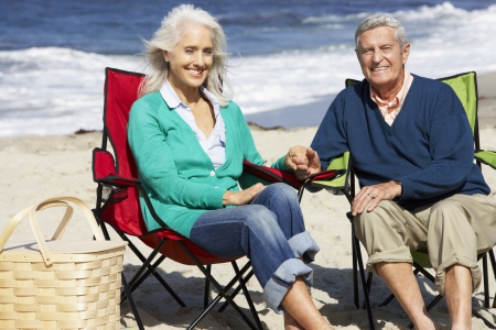 people sitting on chair: Senior Couple Sitting On Beach In Deckchairs Having Picnic Stock Photo