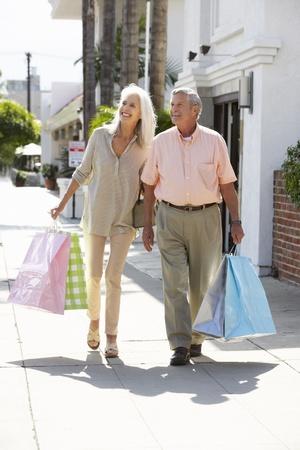 ancianos caminando: Senior pareja con bolsas de compras