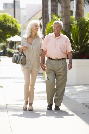 Senior Couple Walking Along Street Together photo