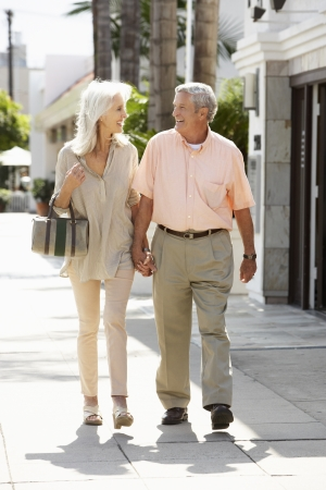 Senior Couple Walking Along Street Together Stock Photo - 18736317