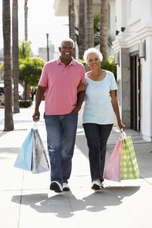 senioren wandelen: Senior koppel uitvoeren boodschappentassen