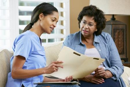 pielęgniarki: PielÄ™gniarka OmawiajÄ…c rekordów z starszych kobiet pacjenta podczas wizyty domowej