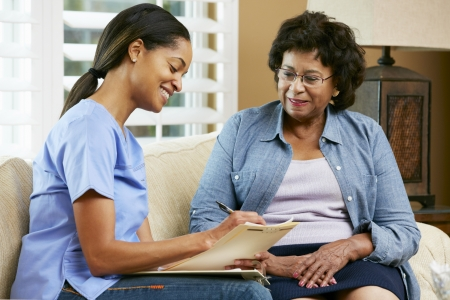 Nurse Making Notes During Home Visit With Senior Female Patient photo