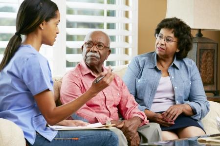enfermera: Enfermera tomando notas durante la visita casa con Senior pareja
