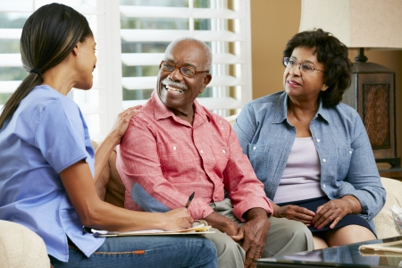 healthcare: Nurse Making Notes During Home Visit With Senior Couple