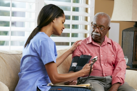 care at home: Nurse Visiting Senior Male Patient At Home Stock Photo