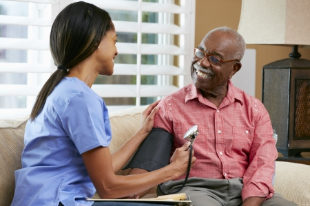 american health care: Nurse Visiting Senior Male Patient At Home Stock Photo