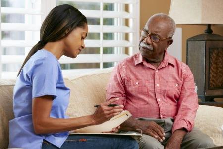 care at home: Nurse Discussing Records With Senior Female Patient During Home Visit Stock Photo