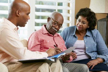home planning: Financial Advisor Talking To Senior Couple At Home