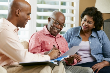 Financial Advisor Talking To Senior Couple At Home photo