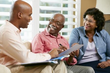 firmando: Asesor Financiero Talking To Senior pareja en el hogar