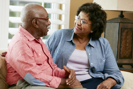 Happy Senior Couple Sitting On Sofa At Home photo