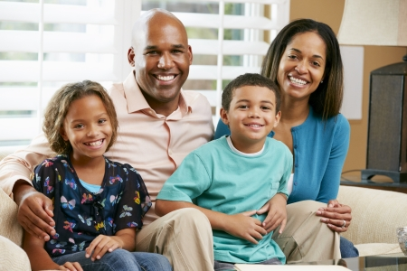 happy black woman: Portrait Of Family Sitting On Sofa Together