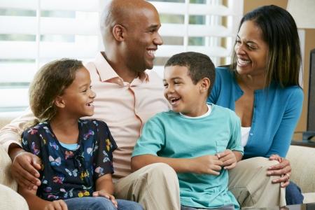 padres hablando con hijos: Familia sentada en el sof�, junto Foto de archivo