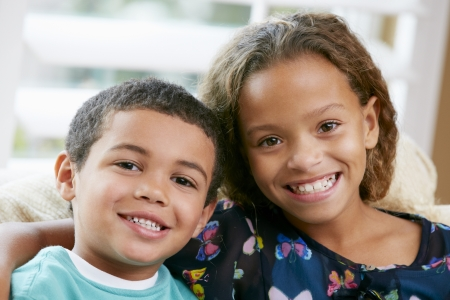 5 10 year old girl: Portrait Of Brother And Sister Sitting On Sofa Together