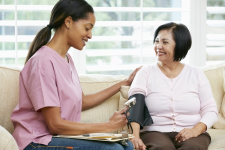 home care nurse: Nurse Visiting Senior Female Patient At Home