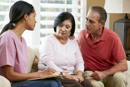 hombre preocupado: Enfermera tomando notas durante la visita casa con Senior pareja