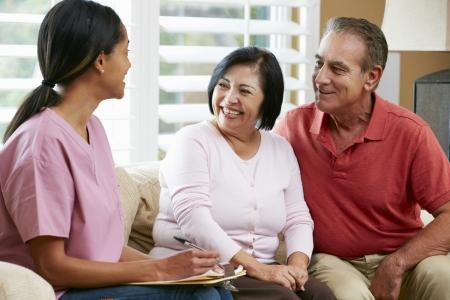 Enfermera tomando notas durante la visita casa con Senior pareja