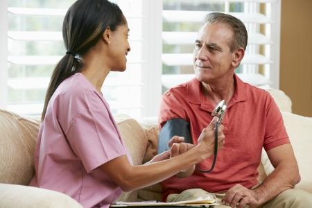 Nurse Visiting Senior Male Patient At Home photo