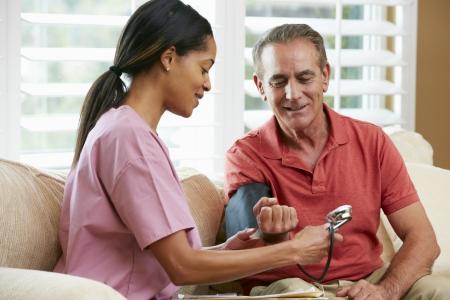 enfermera: Visiting Nurse paciente senior masculino en el hogar Foto de archivo