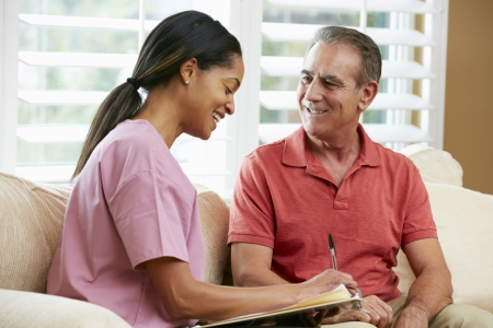 dos personas conversando: Enfermera con el paciente Discutir Registros Senior masculino Durante Visita Domiciliaria