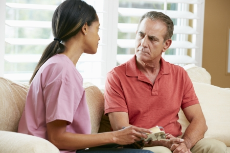 Nurse Discussing Records With Senior Male Patient During Home Visit photo