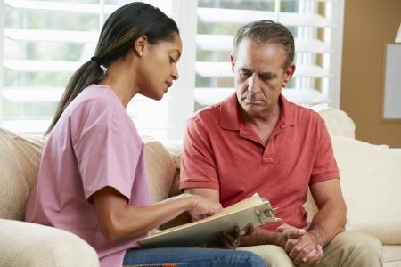 dos personas platicando: Enfermera con el paciente Discutir Registros Senior masculino Durante Visita Domiciliaria
