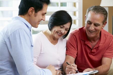 Financial Advisor Talking To Senior Couple At Home photo