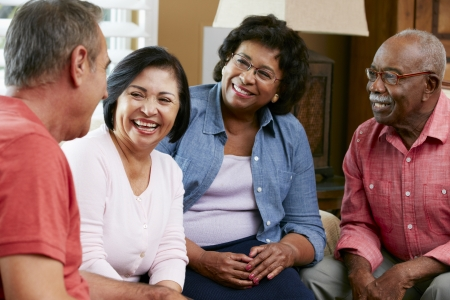 multi racial groups: Group Of Senior Friends Chatting At Home Together