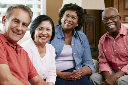 multi racial groups: Portrait Of Senior Friends At Home Together Stock Photo