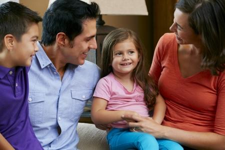niños conversando: Familia que se sienta en el sofá en casa Juntos Foto de archivo