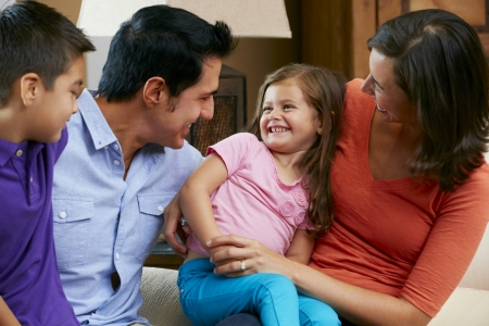 Family Sitting On Sofa At Home Together photo