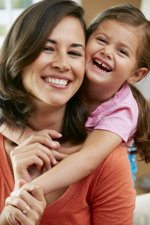 hispanic women: Portrait Of Mother And Daughter Sitting On Sofa At Home Stock Photo