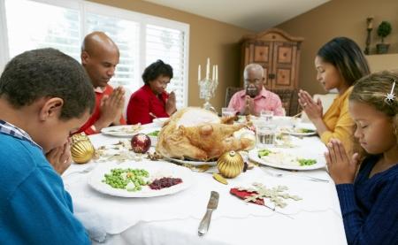 familia orando: Generaci�n de la familia multi Celebrando Navidad Con Alimentos Foto de archivo