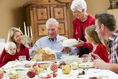 abuelos: Generaci�n de la familia multi Celebrando Navidad Con Alimentos Foto de archivo