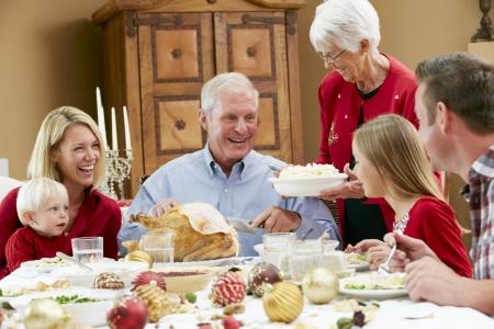 cena navide�a: Generaci�n de la familia multi Celebrando Navidad Con Alimentos Foto de archivo