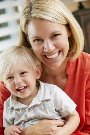 18 to 30s: Portrait Of Mother And Son Sitting On Sofa At Home Stock Photo