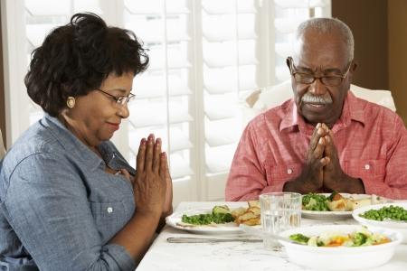 mujeres orando: Senior pareja dar gracias antes de comer en casa