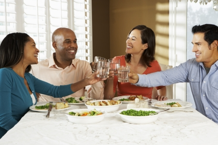 man drinking water: Group Of Friends Enjoying Meal At Home